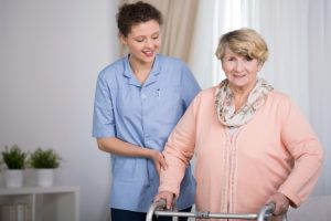Senior woman and supporting nurse