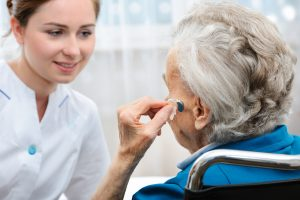 Senior woman inserts hearing aid in her ear learning about Cognitive Decline in Seniors from nurse