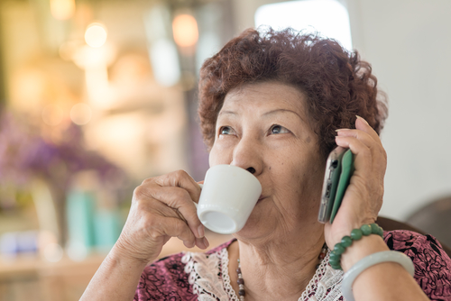 Happy Asian senior woman drinking tea at home.
