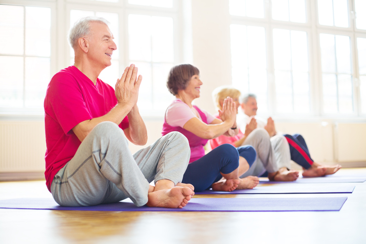 Group of happy seniors practising yoga for senior health