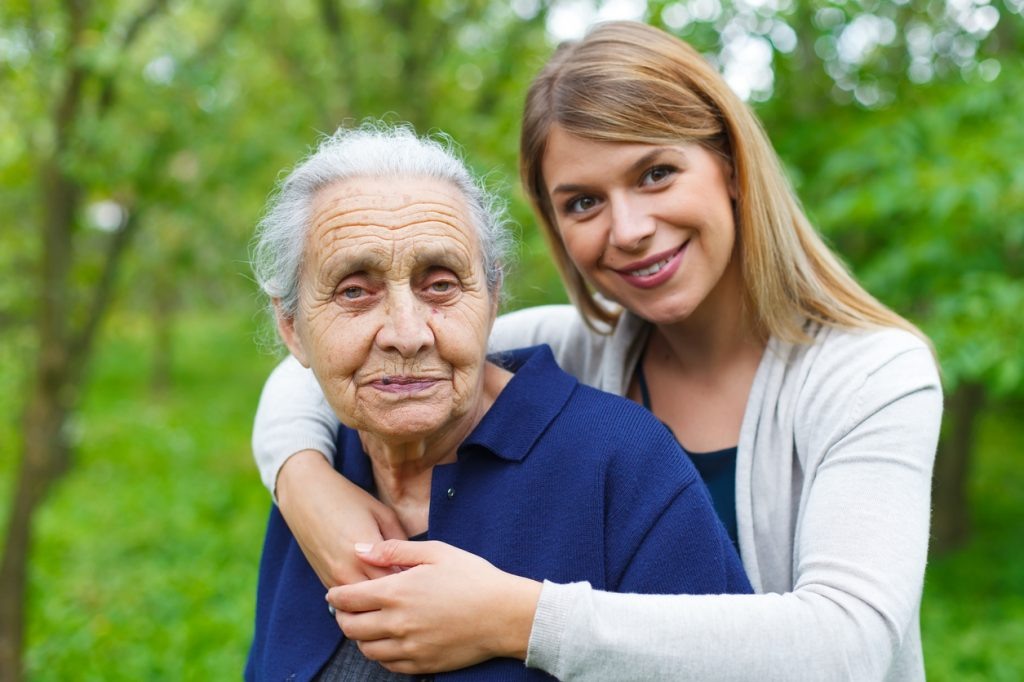 Portrait of a young woman holding her happy grandmother