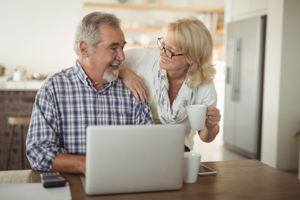Senior couple using laptop to discuss eldercare planning at home