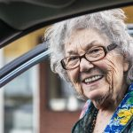 An elderly woman is smiling as she enters through the front passenger door of a car. Uber ride-sharing for seniors concept