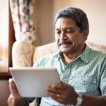 Shot of a senior man using his digital tablet while relaxing at home, use of technology to improve quality of life