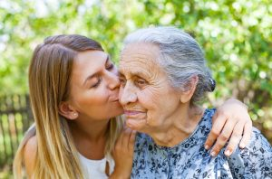 Young woman kissing her old grandmother in the park. Living with dementia concept