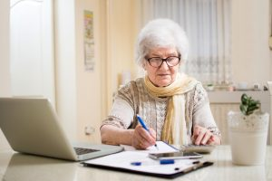 Senior woman making a list at home