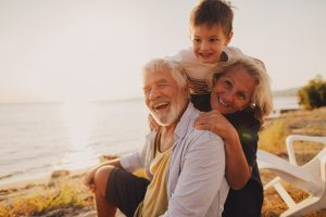 Photo of a little boy and his grandparents having a picnic by the seaside. Seniors on family vacations concept