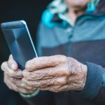 Senior man using mobile phone with hearing aid apps