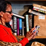 Senior woman on a smart device in her office