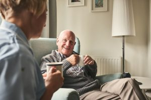 Smiling senior man with cup of coffee talking to female caregiver sitting in front at care home. Aging in Place