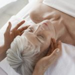 Woman enjoying a facial massage, showing the importance of touch for seniors.