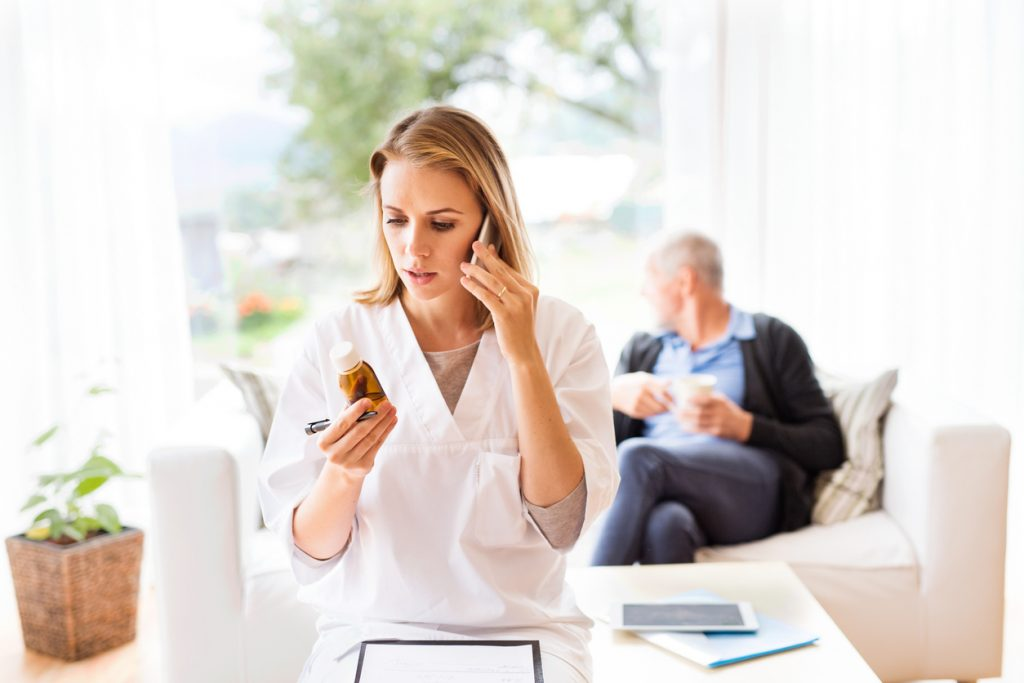 Health visitor with smartphone and a senior man during home visit. A female nurse or a doctor making a phone call. long-distance caregiving concept