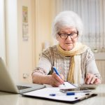 Senior woman making a list at home to ensure successful aging in place