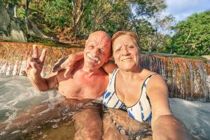 Senior happy couple taking selfie at a hot springs mineral bath- Relax concept to Philippines wonders and active elderly traveling around the world - Warm afternoon color tones with tilted horizon