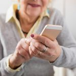 Senior woman holding smartphone in hands and exploring new technology