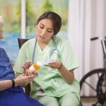 Elderly female patient talks with her Latin descent home healthcare nurse about treatment options in nursing home or home setting. Doctor or nurse gives prescription medication to woman.