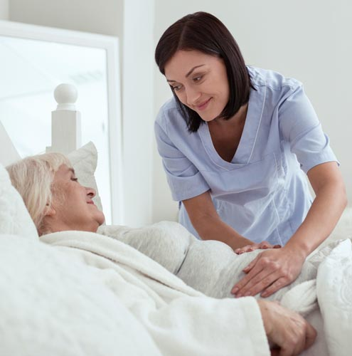 home health aide comforting senior woman with gastrointestinal pain